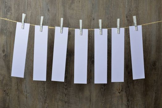 seven sheets of paper hanging on a clothesline