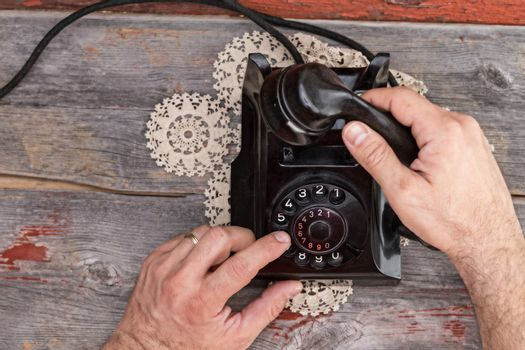 Man dialing out on an old rotary telephone