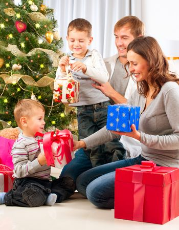 Christmas Family. Children Opening Gifts. Christmas tree