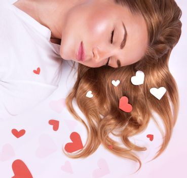 Portrait of sweet female lying down on white floor with closed eyes, sleeping and see romantic dreaming, Valentine day concept