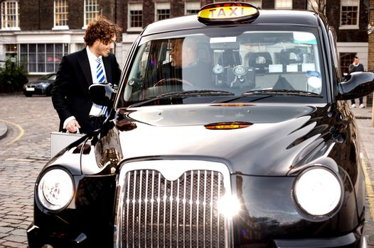 Corporate guy interacting with taxi driver