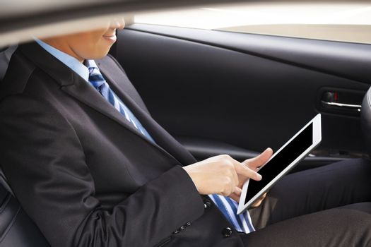 businessman touching tablet in the car