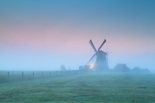 windmill in fog at sunrise