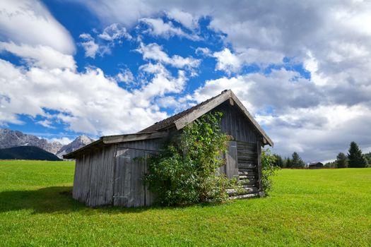 wooden hut on green alpine meadows