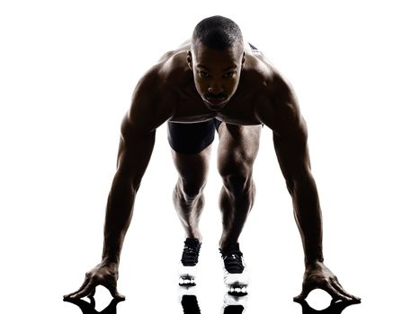 young african muscular build man on starting blocks silhouette