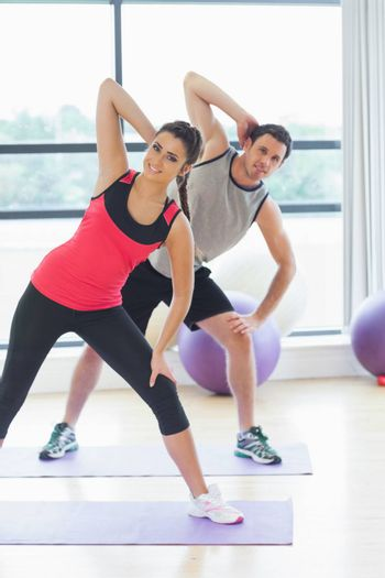 Portrait of two smiling people doing power fitness exercise at yoga class in fitness studio