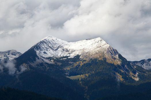snowy mountain peak in clouds