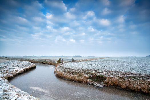 frozen canal on Dutch winter farmland