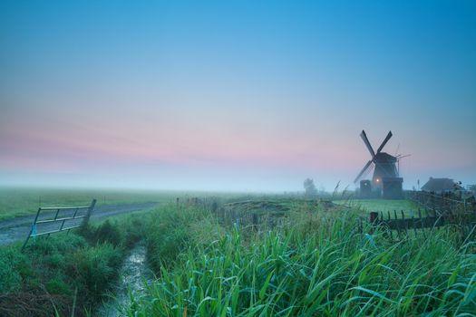 sunrise over Dutch farmland with windmill