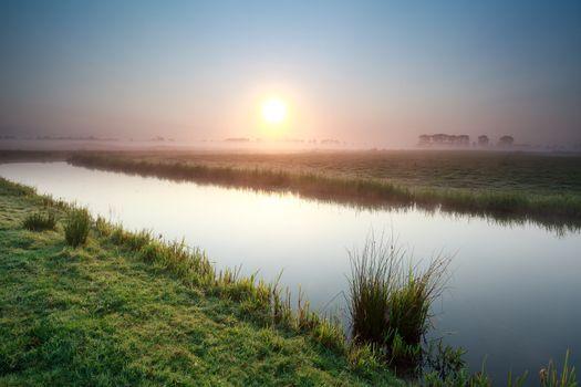 sunrise over river on Dutch farmland