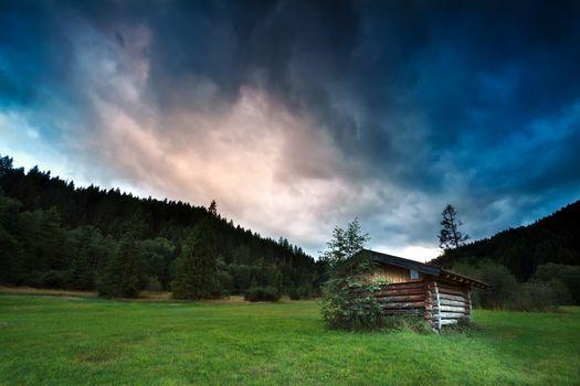 alpine wooden hut during stormy sunset