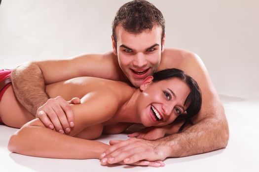 Playful romantic man and woman lying naked on their stomachs in each others arms laughing at the camera,