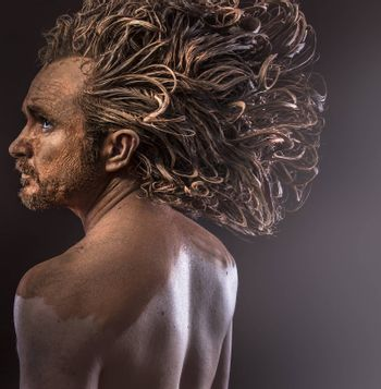 Huge hair, wild man, tribal concept, traditions, body covered with mud