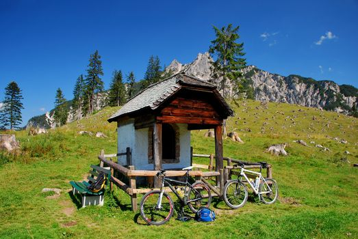 beautiful mountains landscape with cottage and two mountain bike