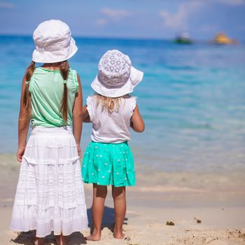 Little adorable girls in nice dress on white beach