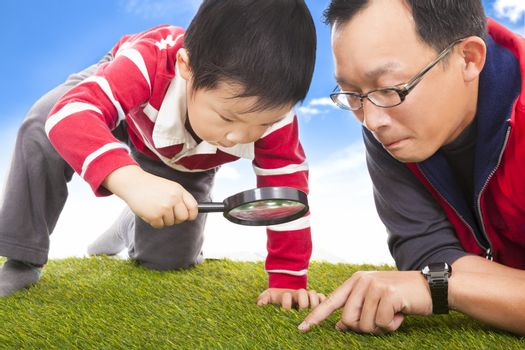 father and kid with magnifying glass to discover