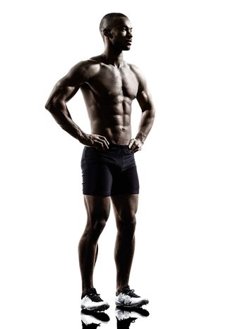 young african shirtless muscular build man standing silhouette