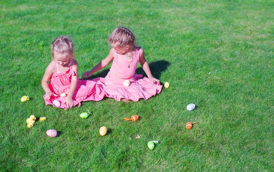 Two adorable little girls playing with Easter Eggs on green grass