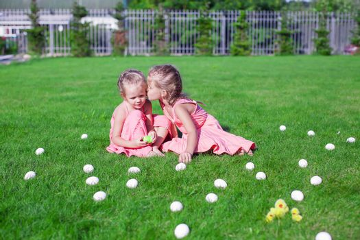 Older sister kissing younger on a green grass of Easter Eggs