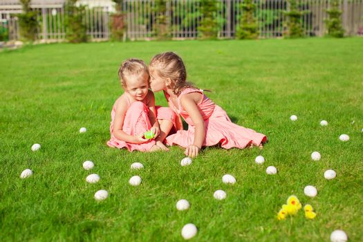 Older sister kissing younger on a green glade of Easter Eggs