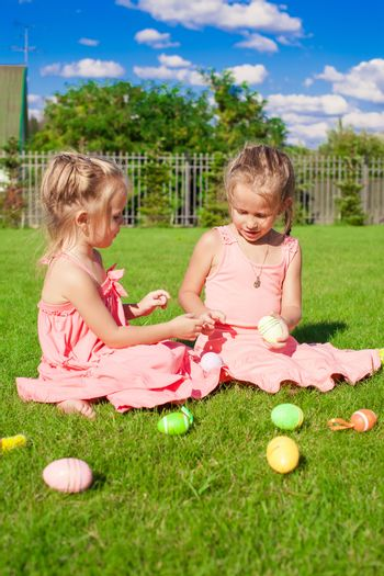 Adorable little girls having fun with Easter Eggs on green grass