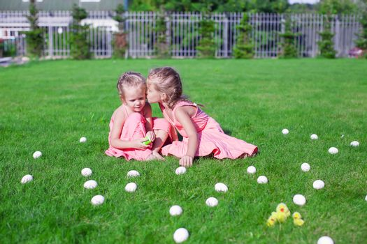 Two adorable little girls having fun with Easter Eggs on green grass