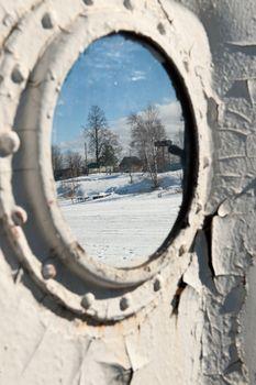 Frozen porthole on the white ships wall.
