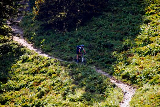 mountain biker on a narrow path in the mountains