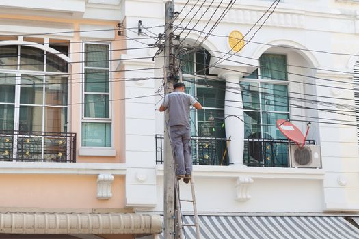 Technician working with cable in front of the house