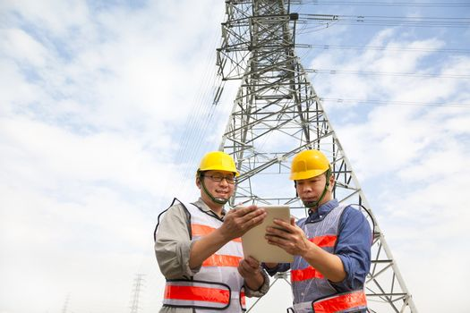 two workers standing before electrical power tower