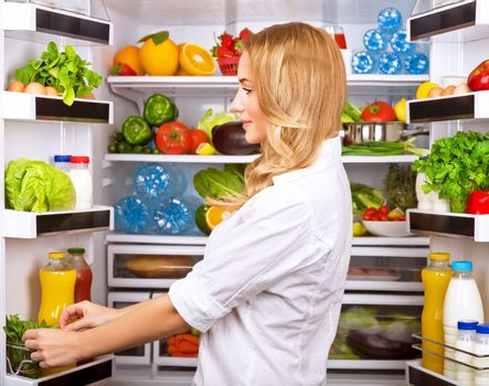 Happy female search something in the fridge