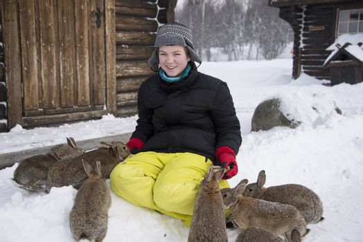 A boy is feeding the rabbits outside on a farm in winter. With snowflakes visible