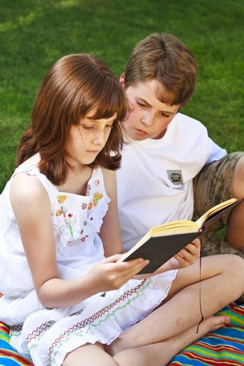 Teenagers.Portrait of cute kids reading books  in natural environment