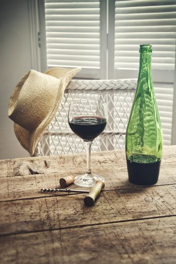 Glass of red wine standing on an old table with straw hat