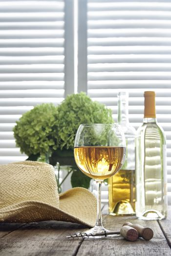 Glass of wine standing on an old table with straw hat
