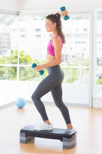 Full length side view of a fit woman performing step aerobics exercise with dumbbells in a gym