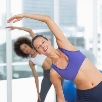 Portrait of two sporty people stretching hands at yoga class in fitness studio