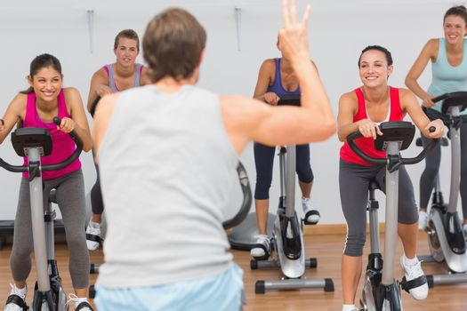 Male trainer and fitness class at spinning class in gym