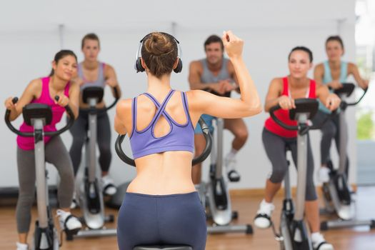 Female trainer and fitness class at spinning class in gym