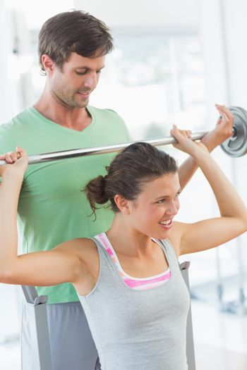 Trainer helping fit woman to lift barbell bench press