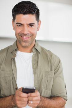 Smiling man text messaging
