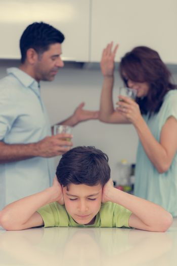 Sad young boy covering ears while parents quarreling
