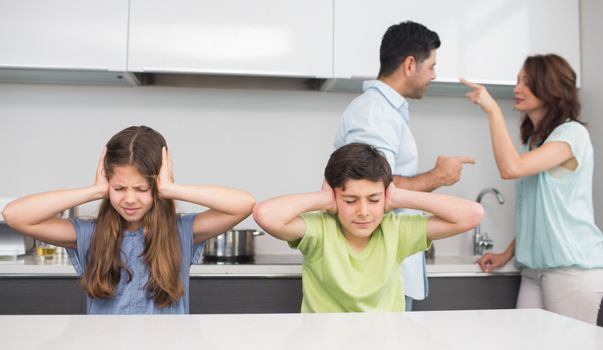 Sad young kids while parents quarreling
