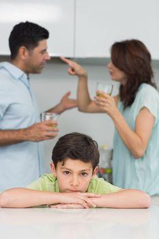 Portrait of a sad son while parents quarreling