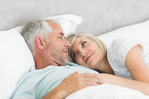 Closeup of a loving mature man and woman lying in bed at the home