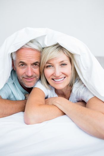Closeup portrait of a mature couple lying in bed at home
