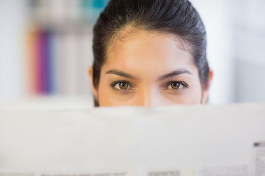 Businesswoman peeking over newspaper