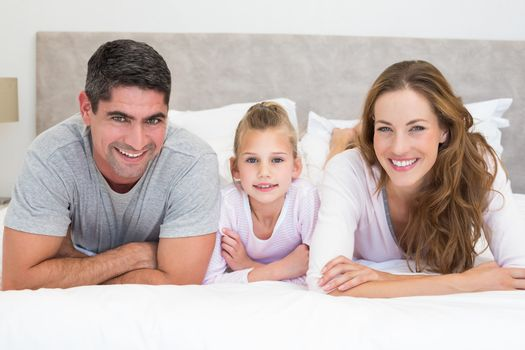 Portrait of happy family in bed