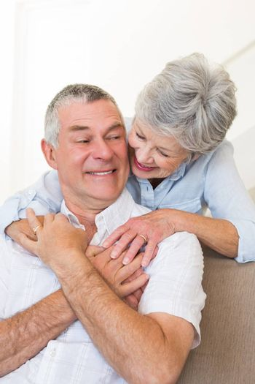 Loving senior woman embracing husband sitting on sofa at home