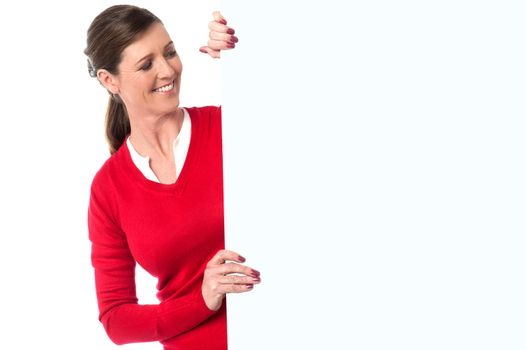 Smiling woman showing blank signboard